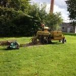 Stubfræsning Holstebro og Struer, stor græsplæne med gul maskine i midten